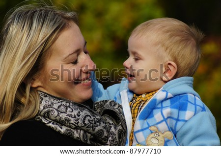 portrait of pretty woman with son at park - stock photo
