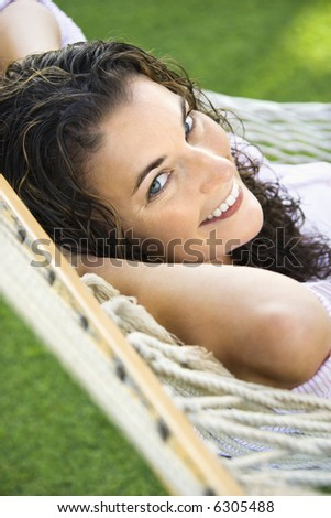 Portrait of pretty young adult Caucasian brunette female lying in hammock smiling up at viewer.
