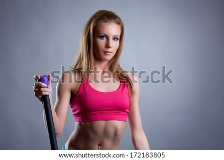 Portrait of pretty young athlete with fitbar - stock photo