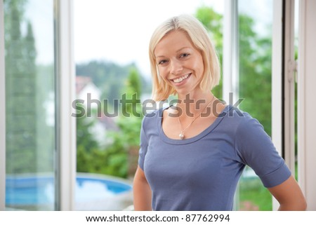 Portrait of pretty young blond woman smiling - stock photo