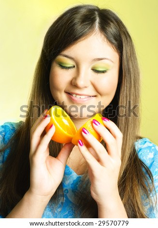 portrait of pretty young brunette woman with an orange - stock photo