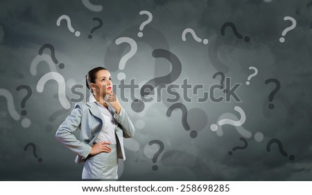 Portrait of pretty young businesswoman and many question marks around - stock photo