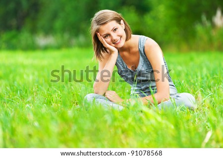Portrait of pretty, young, cheerful woman sitting on green meadow (grass meadow) rests, legs crossed - stock photo