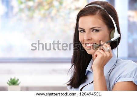 Portrait of pretty young dispatcher smiling, looking at camera. - stock photo