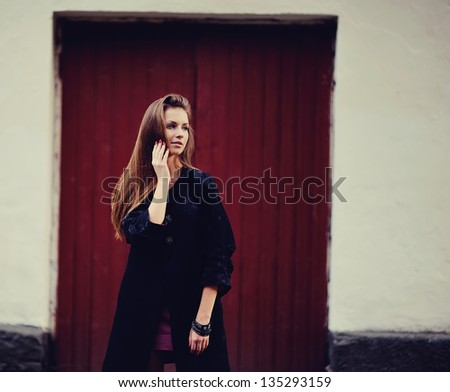 Portrait of pretty young female against red door