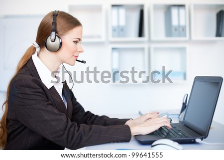 Portrait of pretty young female operator sitting at office desk with headset - stock photo