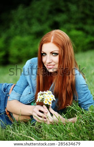 Portrait of pretty young female with daisy - stock photo