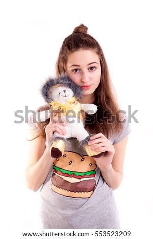 Portrait of pretty young girl holding teddy toy isolated on white