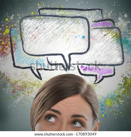 Portrait of pretty young girl looking at dialog symbols overhead - stock photo