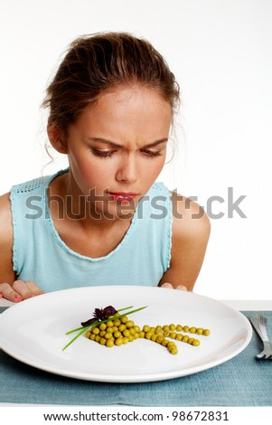 Portrait of pretty young girl looking at pea starter with dislike - stock photo