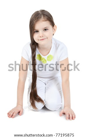 Portrait of pretty young girl sitting on floor over white