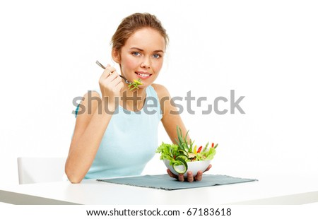 Portrait of pretty young girl with fork and bowl in hands eating vegetable salad - stock photo