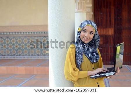 Portrait of pretty young Muslim womanwith notebook and smile - stock photo