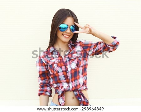 Portrait of pretty young slim woman in sunglasses having fun over white background - stock photo
