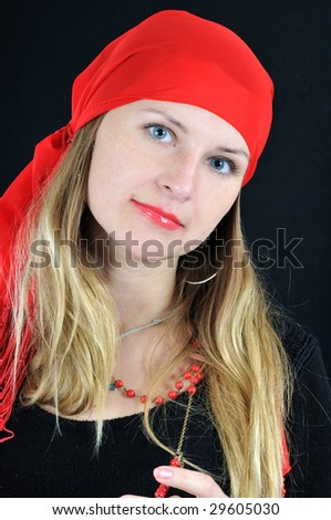 Portrait of pretty young smiling fortuneteller, on black background - stock photo