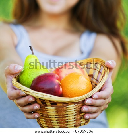 Portrait of pretty young smiling woman wearing grey t-shirt and holding basket full of ripe fruits at summer green park. - stock photo