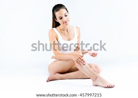 Portrait of pretty young woman applying body cream on legs. - stock photo