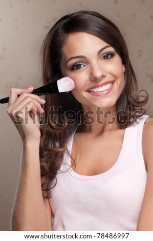 Portrait of pretty young woman applying cosmetic paint brush - stock photo