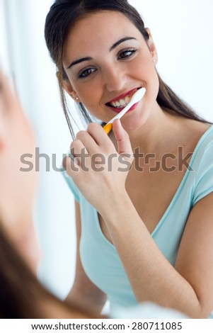 Portrait of pretty young woman brushing her teeth. - stock photo