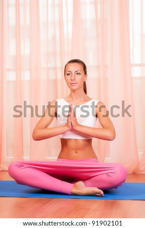 Portrait of pretty young woman doing yoga exercise on mat - stock photo