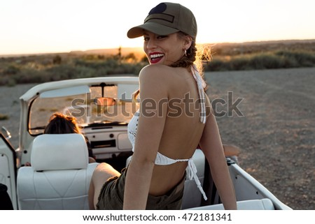 Portrait of pretty young woman driving on road trip on beautiful summer day.