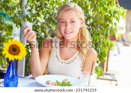 Portrait of pretty young woman eating tuna salad at restaurant - stock photo