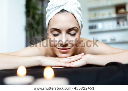 Portrait of pretty young woman enjoying massage at beauty spa. - stock photo