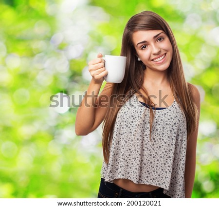 portrait of pretty young woman holding a coffee cup - stock photo