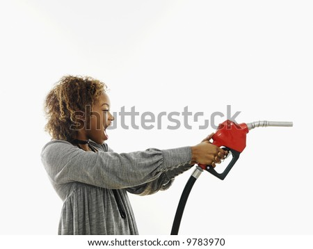 Portrait of pretty young woman holding gas pump nozzle like a gun making angry facial expression on white background. - stock photo