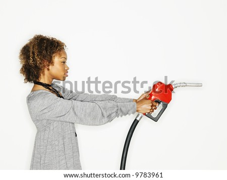 Portrait of pretty young woman holding gas pump nozzle like a gun on white background. - stock photo