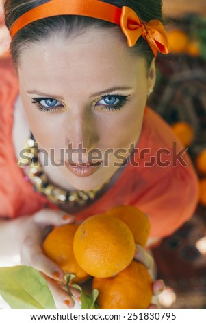 Portrait of pretty young woman holding  orange at summer green park. Shallow dof. - stock photo