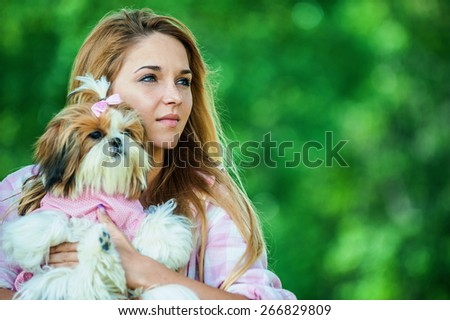 Portrait of pretty young woman holding small fluffy dog, against background of summer green park