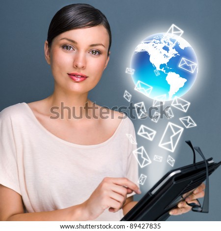 Portrait of pretty young woman holding Touch Screen tablet computer and working with her mail