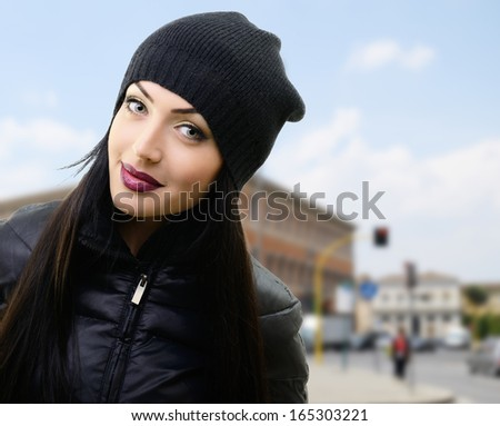 portrait of pretty young woman in black hat and jacket over urban background - stock photo