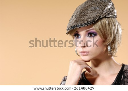 Portrait of pretty young woman in cap posing  - stock photo