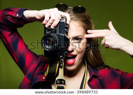 Portrait of pretty young woman taking photos with a retro camera. - stock photo