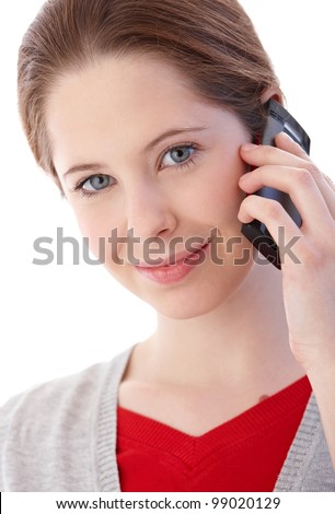 Portrait of pretty young woman talking on mobile phone, smiling. - stock photo