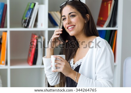 Portrait of pretty young woman using her mobile phone in the office. - stock photo