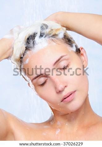 Portrait of pretty young woman washing her hair - close-up - stock photo