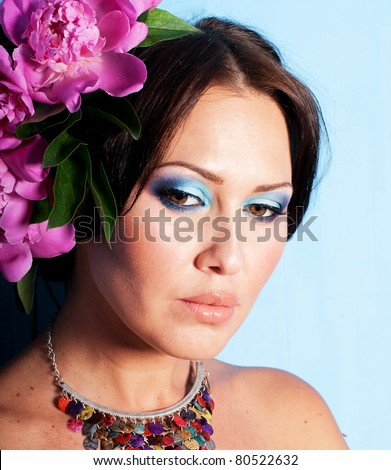 portrait of pretty young woman with art make up and flowers - stock photo