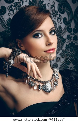 Portrait of pretty young woman with beads and bangle - stock photo