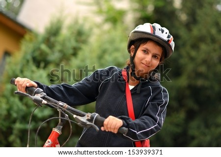 Portrait of pretty young woman with bicycle in a park
