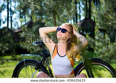 Portrait of pretty young woman with bicycle in a park smiling - Outdoor - stock photo