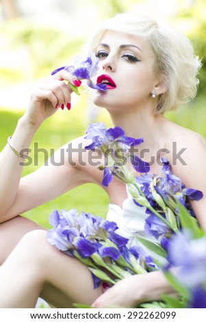 Portrait of pretty young woman with blonde short hair and bright makeup sitting and smelling blue violet iris flowers on outdoor background, vertical picture - stock photo