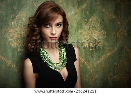 Portrait of pretty young woman with green beads
