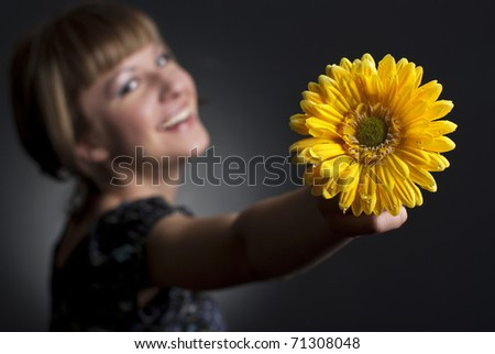 portrait of pretty young woman with yellow flower - stock photo