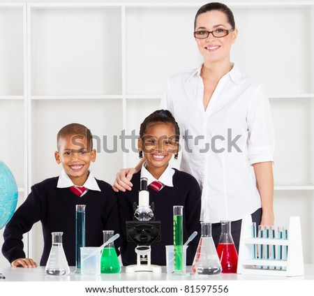 portrait of primary teacher and students in science class - stock photo