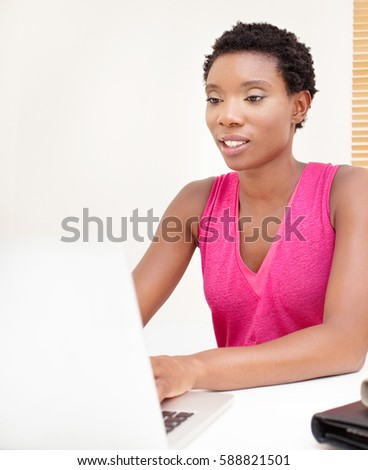 Portrait of professional african american business woman at home desk working with laptop computer, typing in office, smiling indoors. Black entrepreneur using technology, white space, lifestyle.