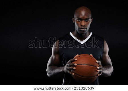 Portrait of professional african basketball player holding a ball looking at camera. Fit young man with basketball against black background with copyspace. - stock photo