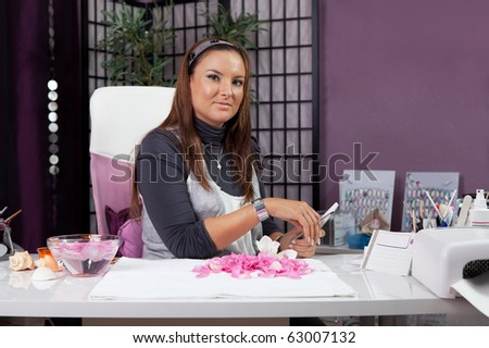 Portrait of professional beautician in her nail studio - stock photo